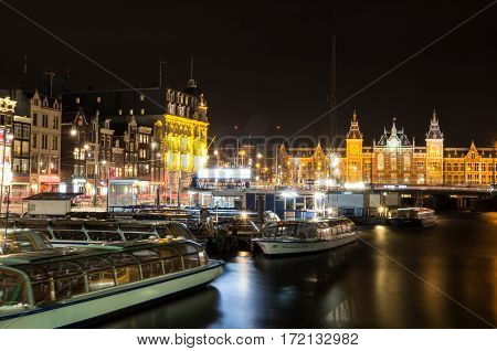 Cityscape of Amsterdam in the Netherlands by night with the central station