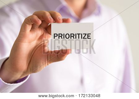 Businessman Holding Card With Text Prioritize