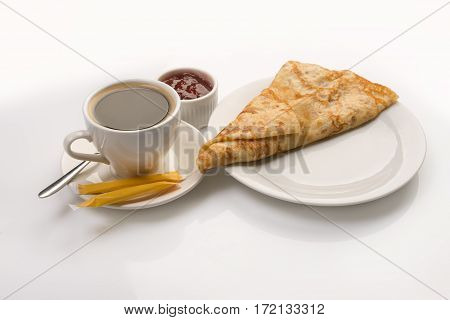 Pancake crepe rolled in triangle form served with jam and full cup of black coffee studio shot on white background.
