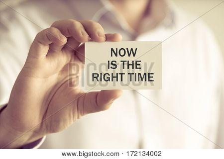Businessman Holding Now Is The Right Time Card