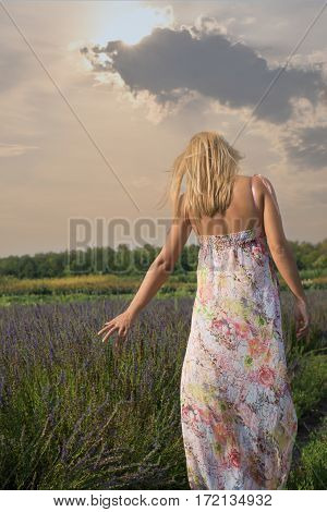 Girl in colorful dress walking through a lavender field at sunset.