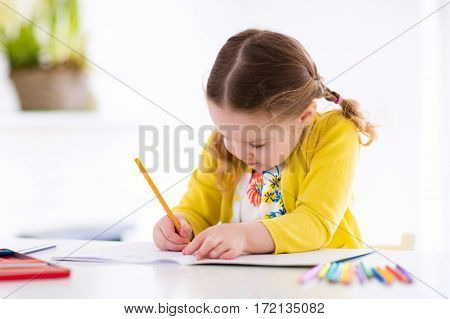 Cute little girl doing homework reading a book coloring pages writing and painting. Children paint. Kids draw. Preschooler with books at home. Preschoolers learn to write and read. Creative toddler