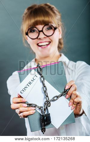 Business concept. Happy woman businesswoman holding in hands paper document contract chained with padlock