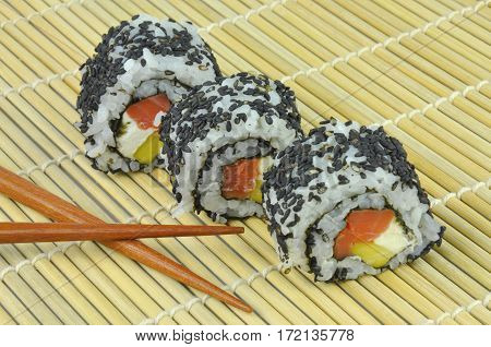 Sushi rolls with salmon, avocado, cream cheese and black sesame