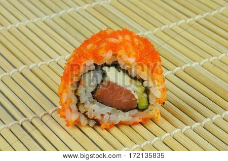 Sushi roll Philadelphia and red masago roe on bamboo mat