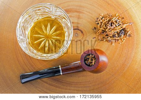 Glass of single malt scotch whisky next to classic blended aromatic pipe tobacco on bright wooden background