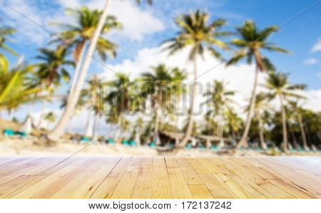 Blurred palm trees at tropical coast with wooden floor