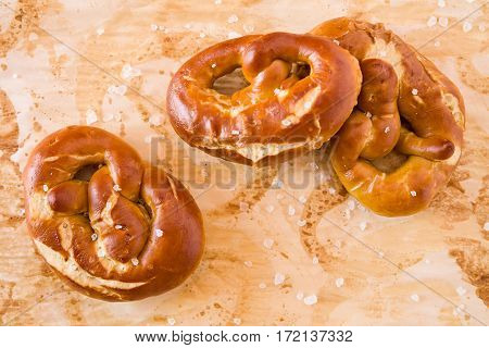 Several salty cooked pretzel seen from above over the greaseproof paper