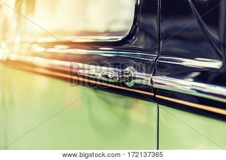 Closeup of a green vintage car in sunlight