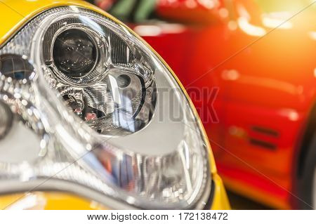 Closeup on an headlight of a yellow sport car
