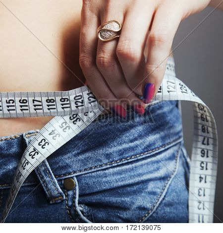 Woman measuring her waistline. The concept of diet and healthy lifestyle.