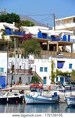 MAKRIGIALOS, CRETE - SEPTEMBER 18, 2016 - Traditional fishing boats in the harbour with town buildings to the rear Makrigialos Crete Greece Europe, September 18, 2016.