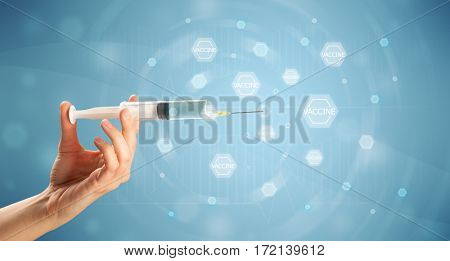 Female doctor hand holding syringe with blue background