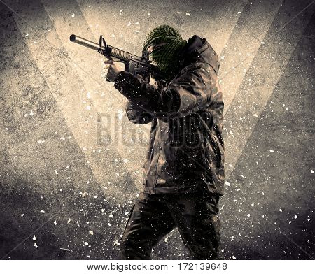 Portrait of a dangerous masked armed soldier with grungy light background