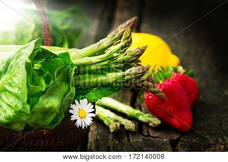 Green Salad with green asparagus and strawberries on an old wood table