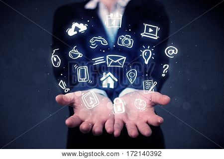 Blue multimedia icons in the hands of a young casual businesswoman