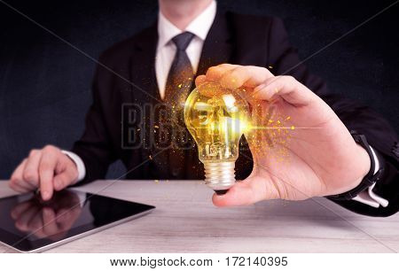 An elegant office worker holding a yellow sparkling light bulb in his hand while working in front of dark blue background concept.