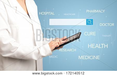 Female doctor holding tablet with blue background and search bar with hovering medical words