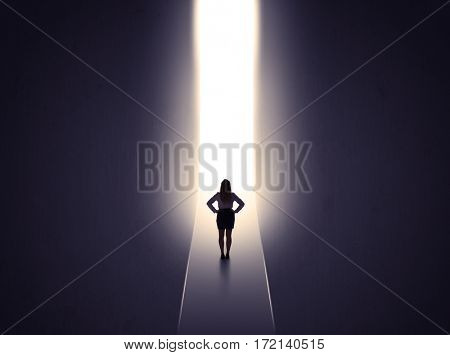 Young businesswoman stands in dark tunnel and looks in the glowing end