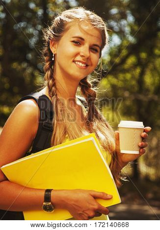 Cute female student with books and cup of coffee (education science  self development)