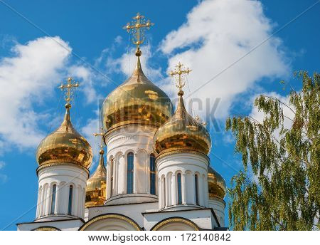 Golden domes and crosses of an orthodox temple against the sky
