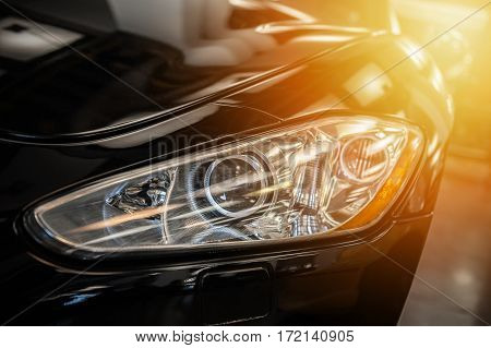 Closeup on an headlight of a black sport car in the sunlight