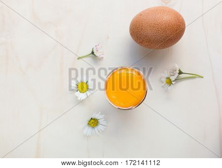 Fresh organic eggs whole and raw yolk. Some daisies on a wooden surface.