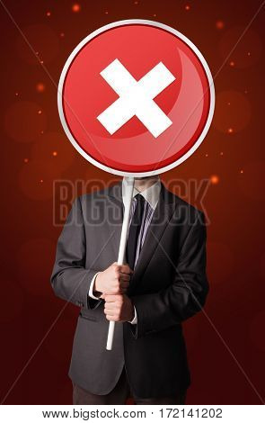 Smart businessman holding round red sign with a white cross