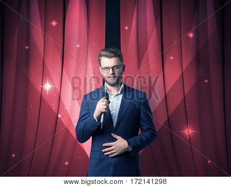 Businessman speaking into microphone with red curtain behind him