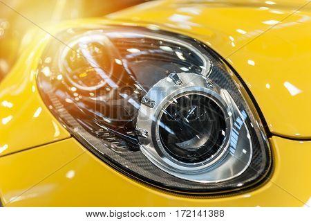 Closeup on an headlight of a yellow sport car in the sunlight