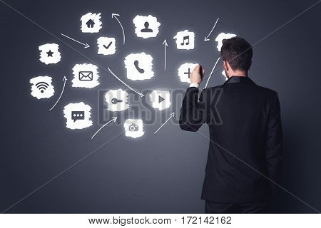 Young businessman in black suit standing in front of white multimedia icons