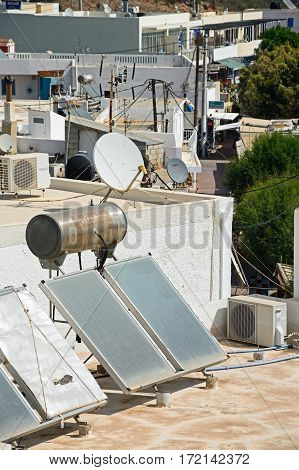MAKRIGIALOS, CRETE - SEPTEMBER 18, 2016 - Water heating solar panels on a building roof Makrigialos Crete Greece Europe, September 18, 2016.