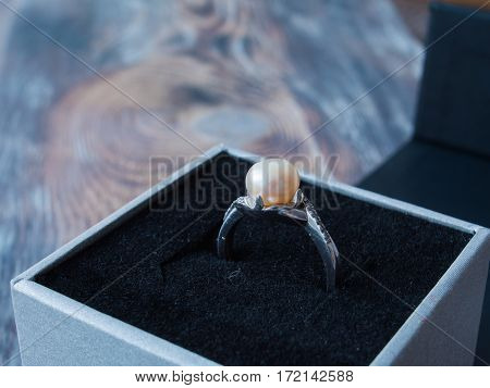 Side view on beautiful pearl ring in black box on wooden background