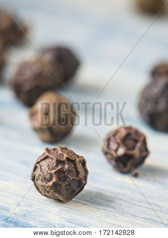 Black pepper peas. Macro close-up. Blue wood background.