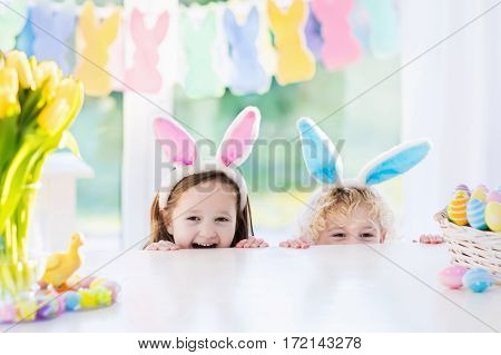Boy and girl in bunny ears at breakfast on Easter morning at table with Easter eggs basket. Kids celebrating Easter. Children on Easter egg hunt. Home decoration pastel bunny banner and flowers.