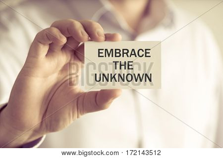 Businessman Holding Embrace The Unknown Message Card