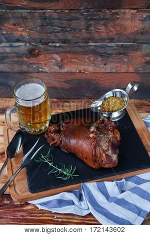 Baked Pork Shank, Rosemary Branch And Honey Sause And Glass Of Beer On A Wooden Table