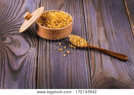 Wooden scoop spoon and bowl full of brown cane sugar with pinch of sugar spilled around on wooden table top view