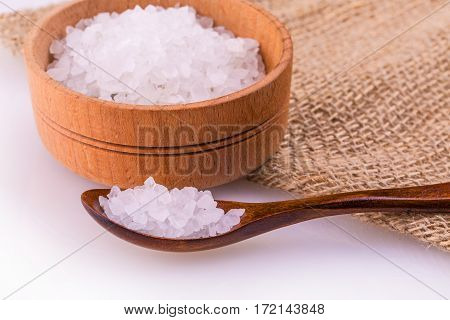 Wooden cup and spoon with a white bath salt on burlap on white background