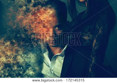 sexy couple creating particle dispersion over a gray background