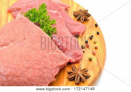 Raw meat with parsley on cutting board isolated on white