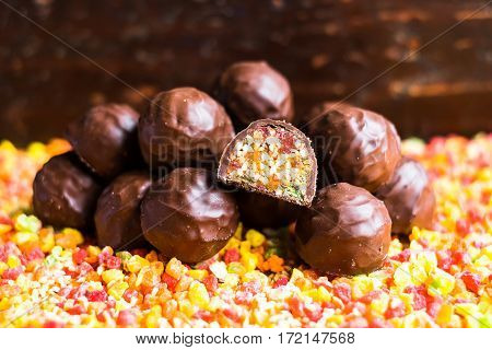 Candied roasted hazelnuts and peanuts with dried apricot, dried cherry, candied pineapple fruit and honey in dark chocolate glaze, selective focus.