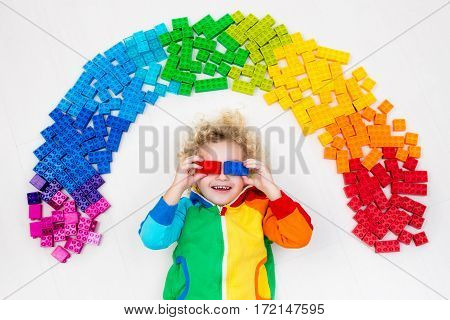 Funny little boy playing with colorful rainbow plastic blocks. Kids play create and learn colors. Educational toys for creative children. Preschooler building block toys. Kid playing on the floor.