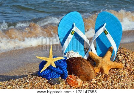 Colorful flip flops starfish coconut and rope on the beach.