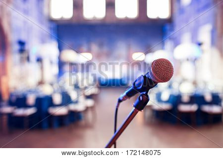 Microphone over the Abstract blurred photo of conference hall or wedding banquet background.
