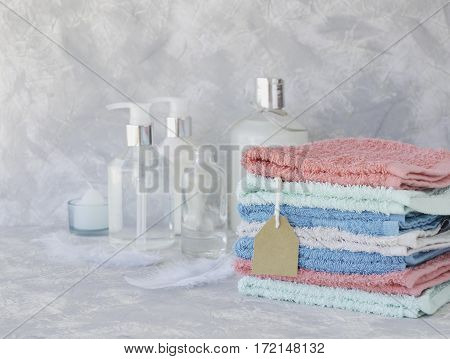 Towel stack with a price tag on a white marble background, space for text, selective focus