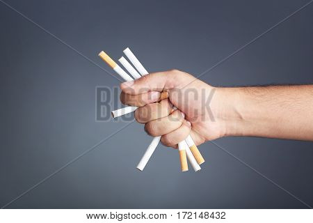 Male hand crushing cigarettes on black background