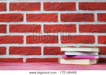 Colorful books on a brick wall background