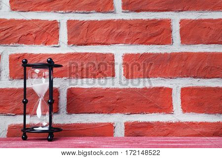 Black Hourglass On The Brick Wall Background