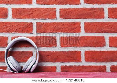 Headphones on the brown brick wall background